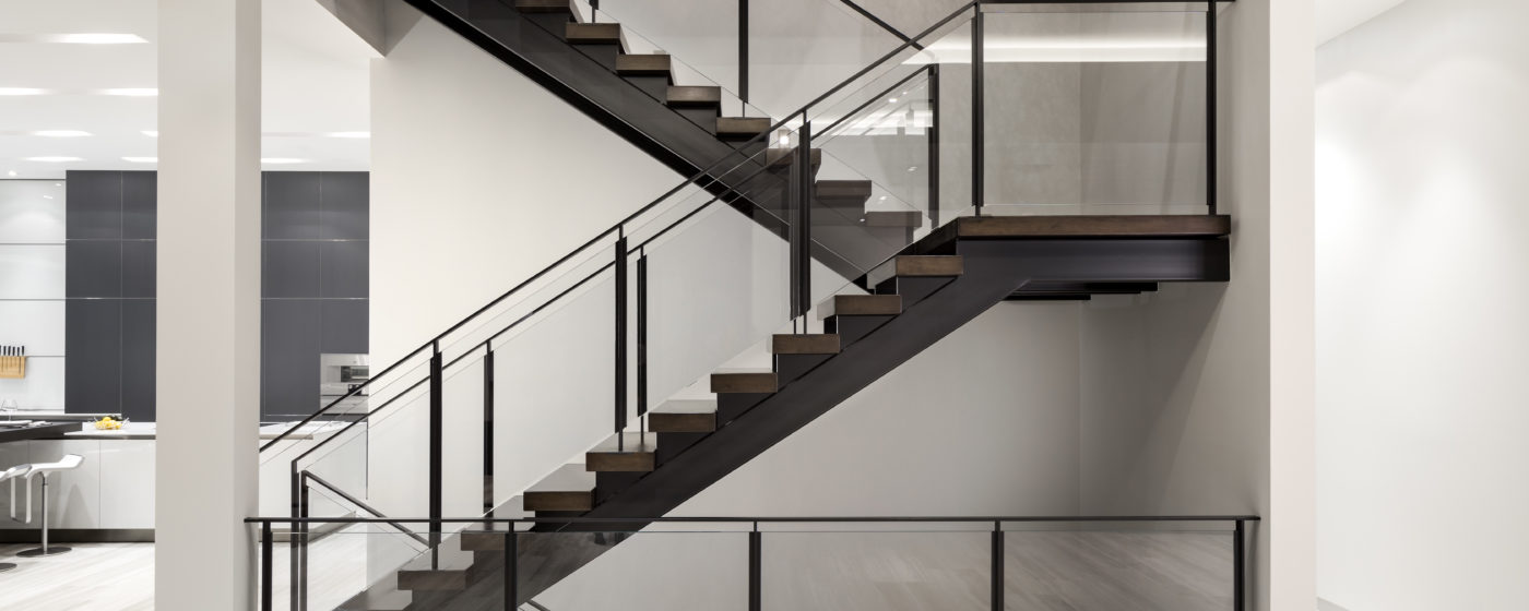 Double stringer stairway with wood steps and glass railing